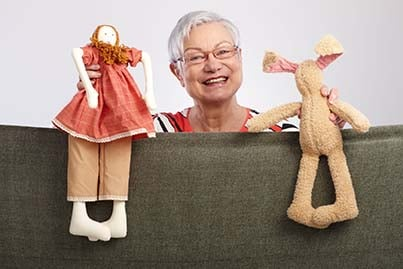 13944846 - happy grandmother presenting a puppet show, smiling   65533;